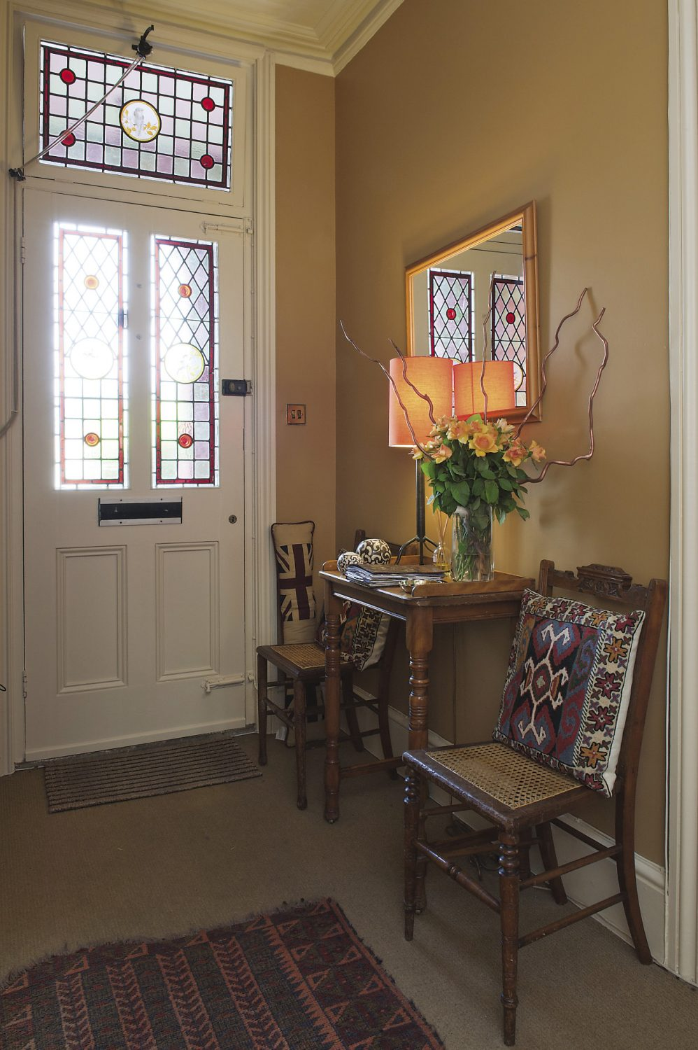 The inviting glow of the colours used in the hallway combined with the stained glass panels, provides a warm welcome to Ann Edwards' Victorian villa