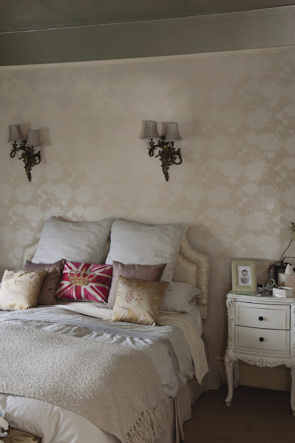 The chrysanthemum wallpaper has a subtle pearlised sheen that is echoed by the silver wash used on the ceiling. The bedlinen is a mix of fine linen and silk but in the centre of the bed is a Union Jack cushion with a crown in the centre