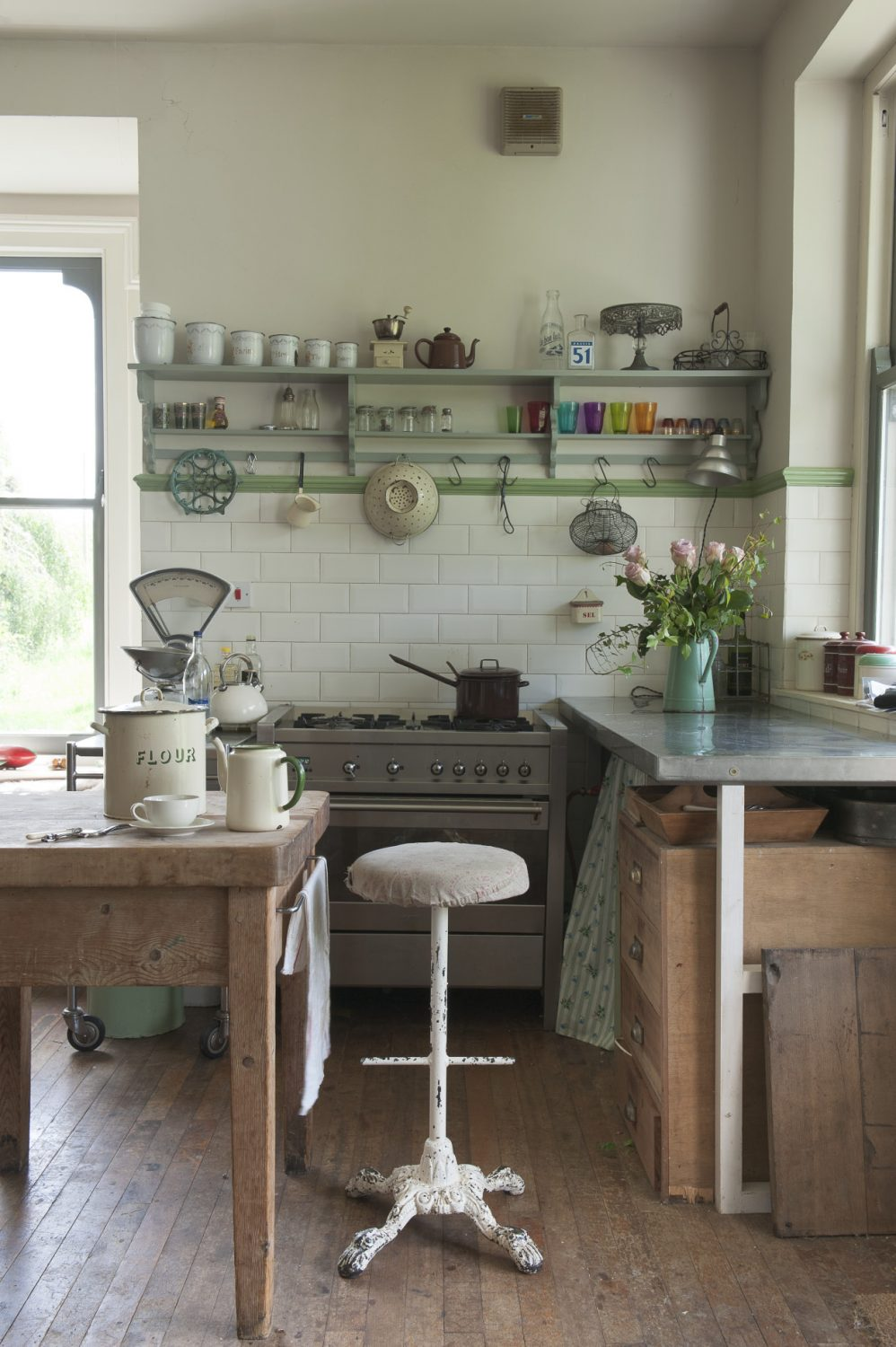 The kitchen is equipped with an assortment of tables and trolleys with under-sink and work surface spaces covered with curtains of cheerful, printed fabrics