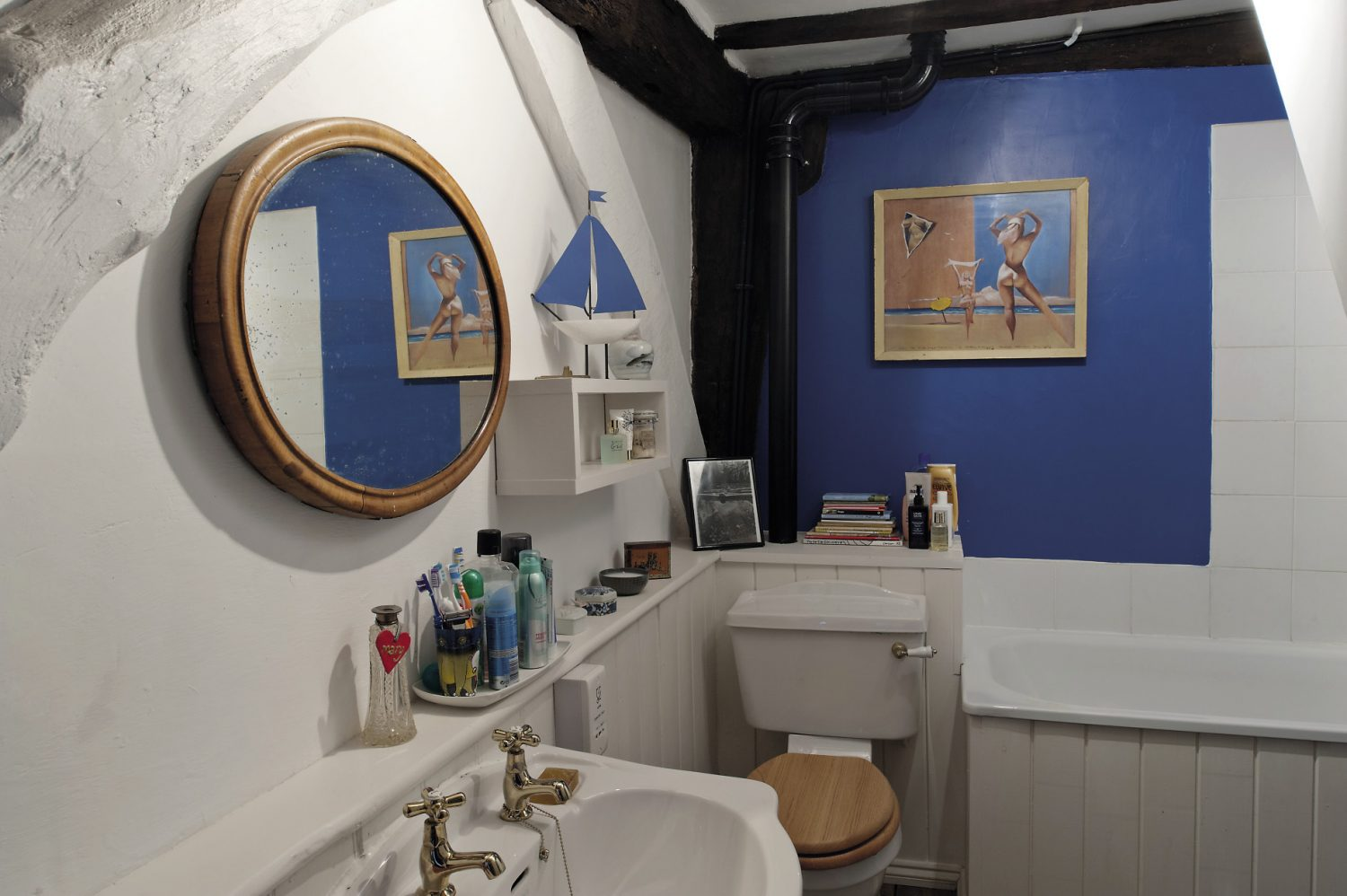 The family bathroom, painted a rich cobalt blue, features artwork collected by David's father