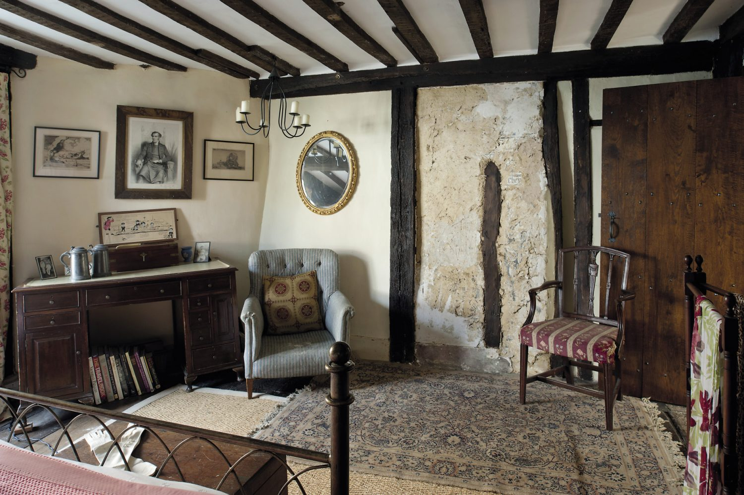 In the guestroom at the front of the house, part of the wallcovering has been scraped away to reveal a panel of pargeting and painting that must date from the 1480s when this house is believed to have been built