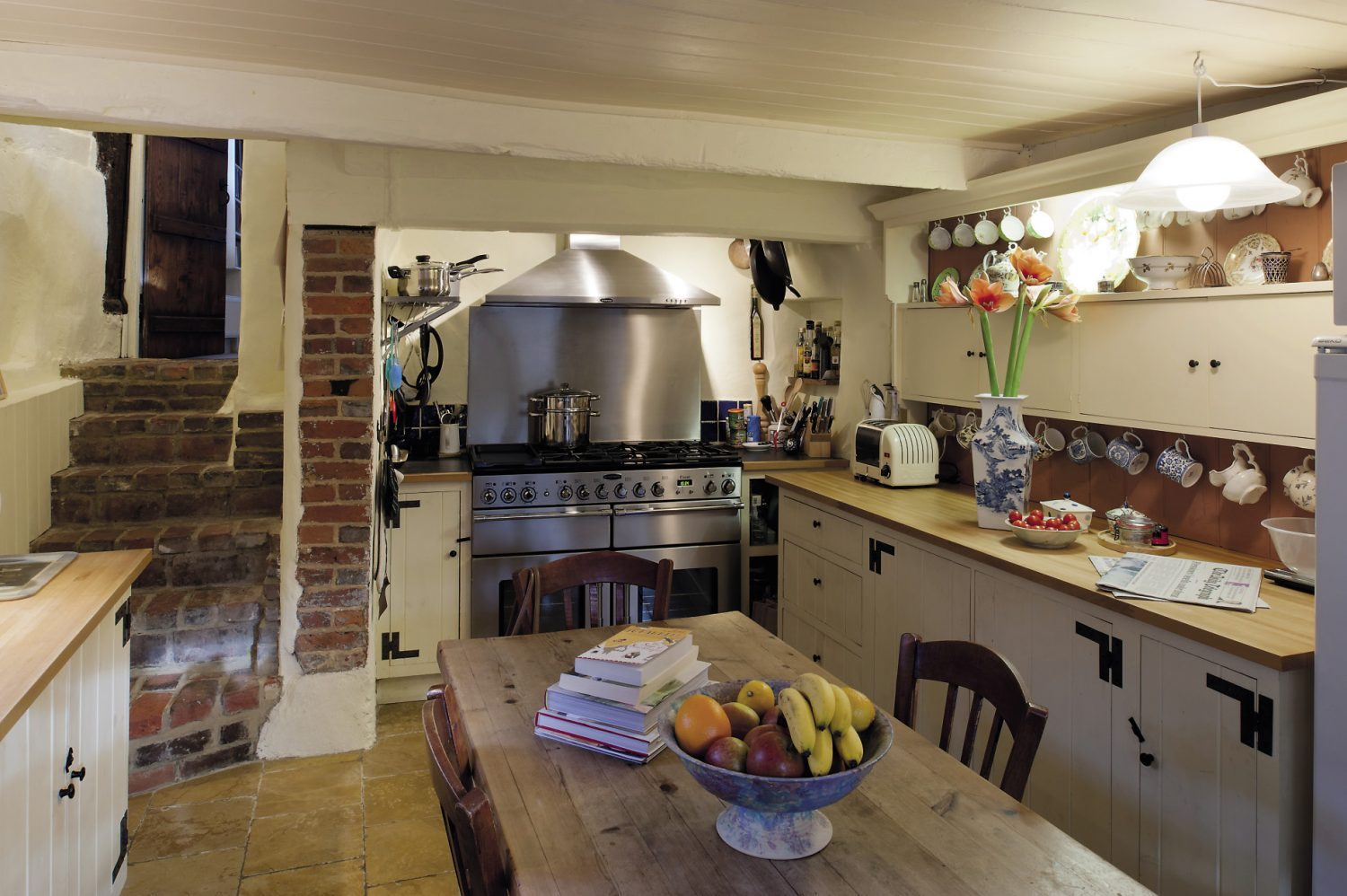 Stone steps lead down from the dining room into the kitchen, which was once a scullery. It has been updated with a huge stainless steel range, but has kept its old country charm, with a polished stone floor and scrubbed pine table