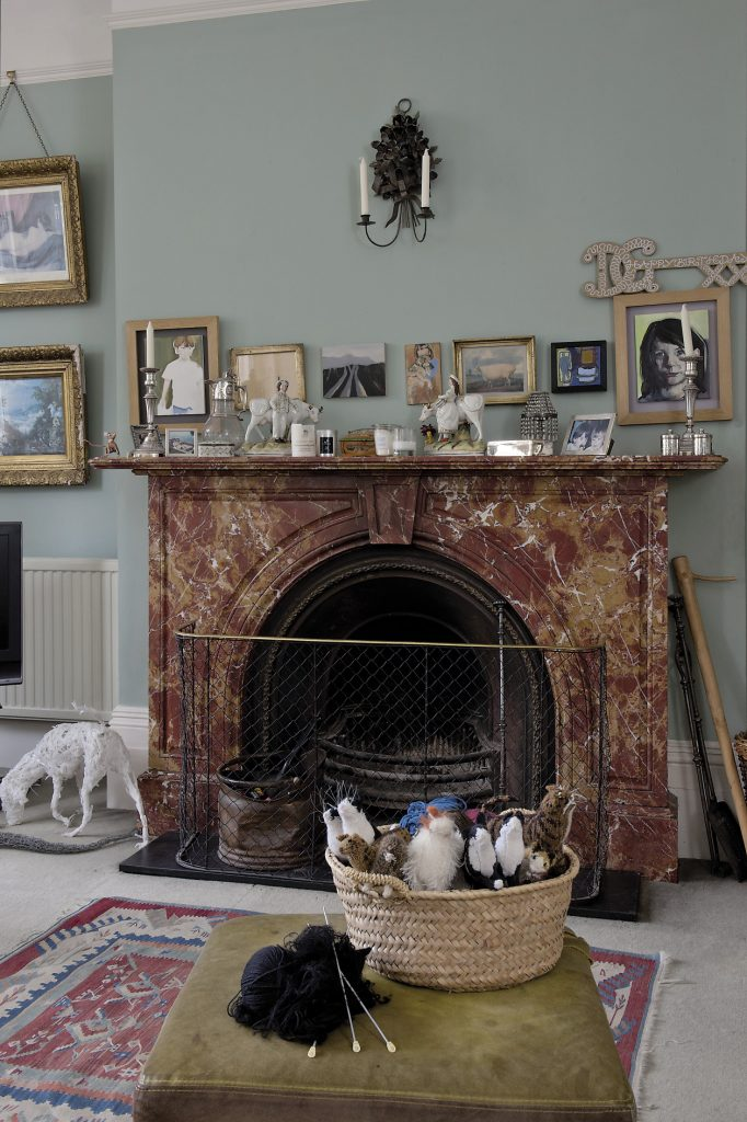 "The drawing room is painted in a gentle blue-green. ""The colour was dictated by the rust red of the fireplace,"" says Joanna. ""It's called liver and bacon marble, apparently, and it's not an easy thing to complement."" To the left of the fireplace stands Dominic Gubb's 'milkdog' sculpture"