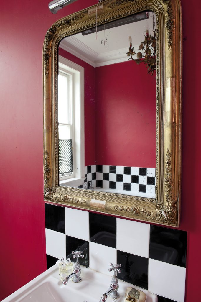 The 'baroque' bathroom features bright red walls accented with black and white chequered tiles