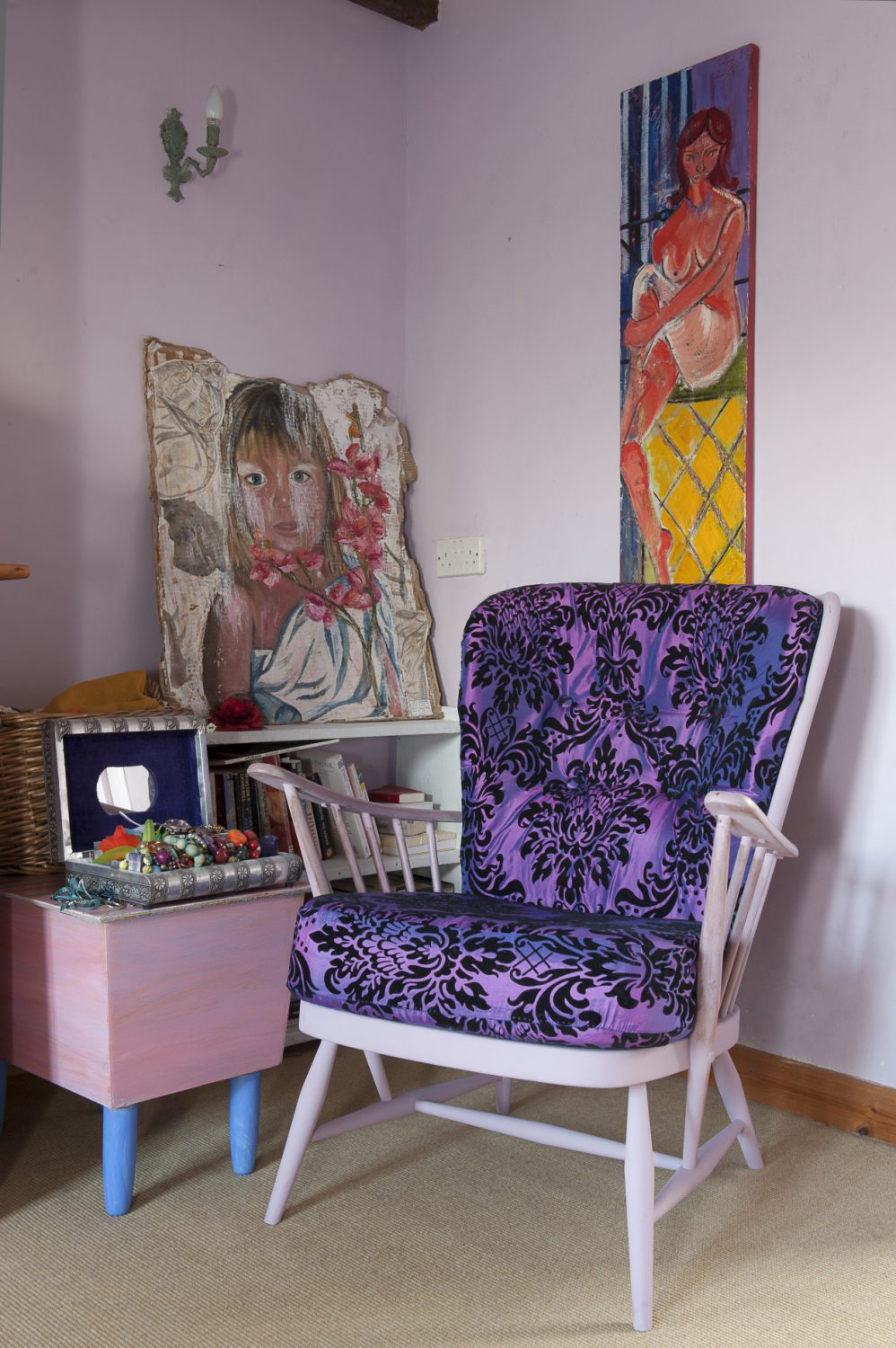 In one corner of Oeda's bedroom, a wooden armchair is upholstered in striking mauve and black. On the walls are more pictures by her daughters and a nude by Kim Langford