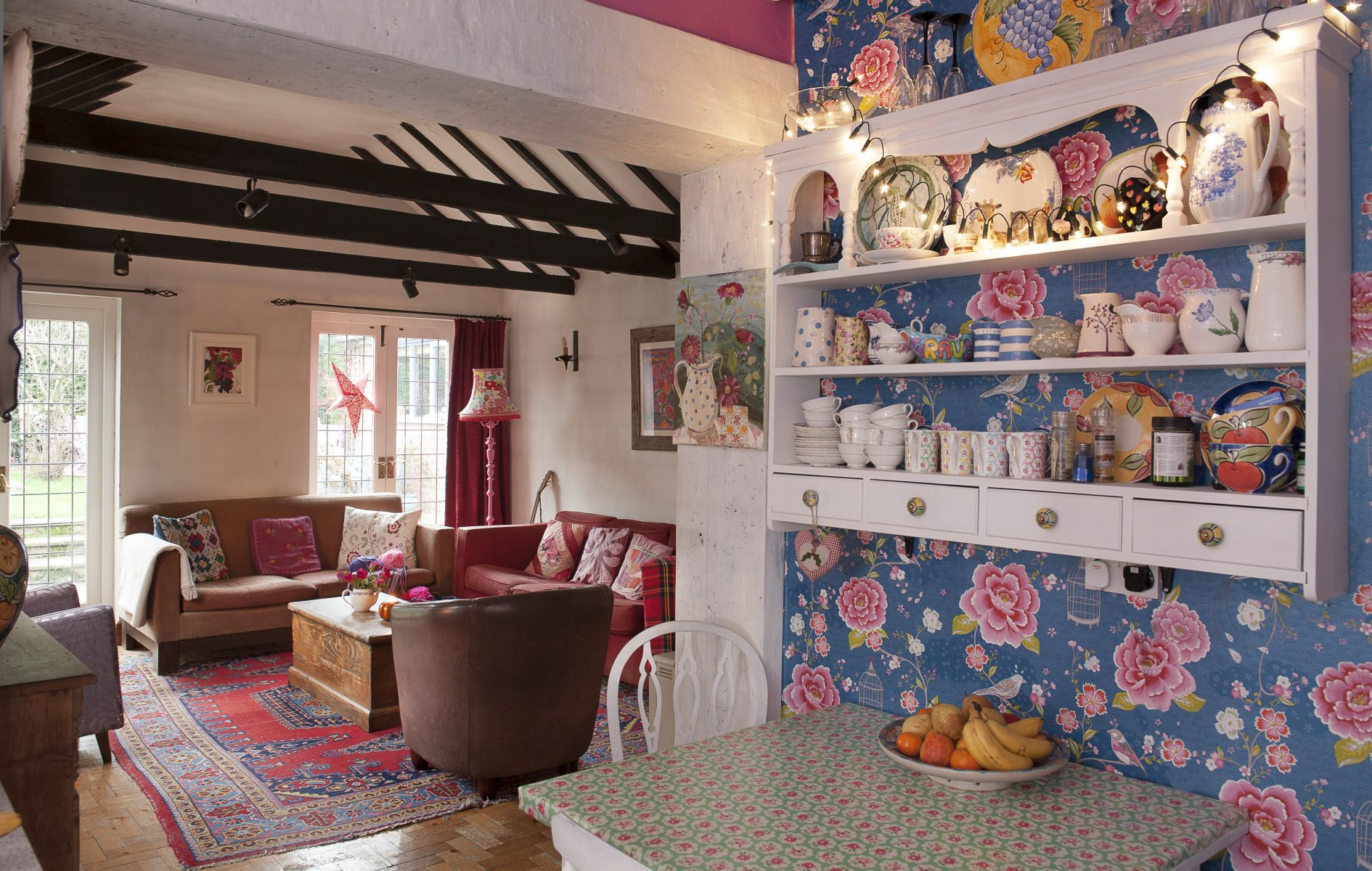 In contrast to the kitchen, the restrained colour-palette of the drawing room is complemented by pops of colour in the form of 'Yolanda' a pink standard lamp created by Oeda, oriental carpeting and a cherry-red sofa and curtains