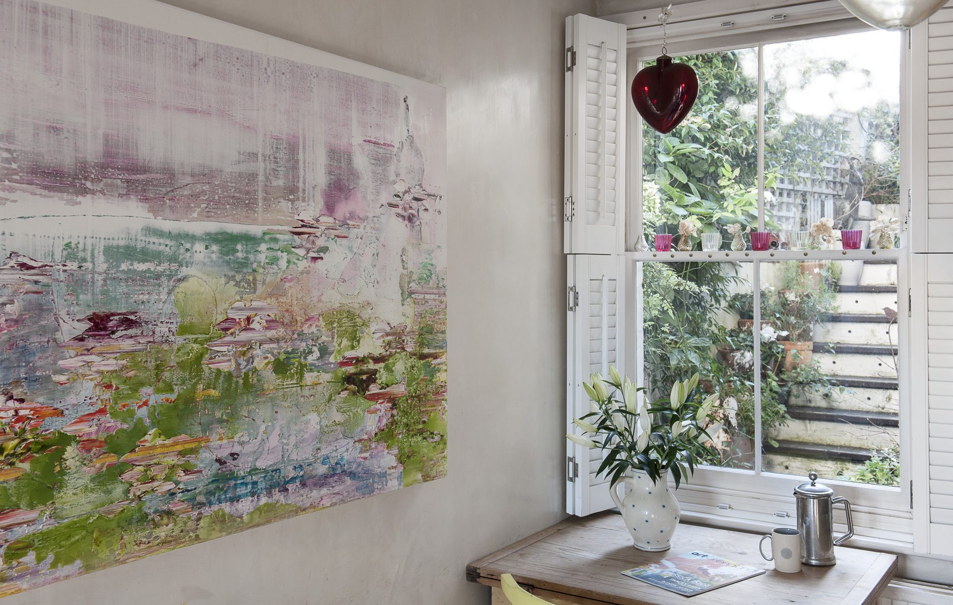 In the corner of the sitting room a window frames the honeysuckled steps that lead up to the garden, creating a natural picture of its own