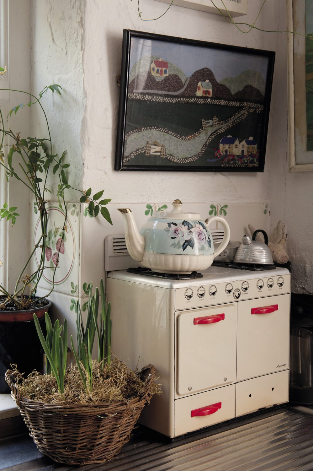 A Lilliputian 1940s enamel miniature cooker, complete with tiny baking sheets and kettle, is tucked into one corner