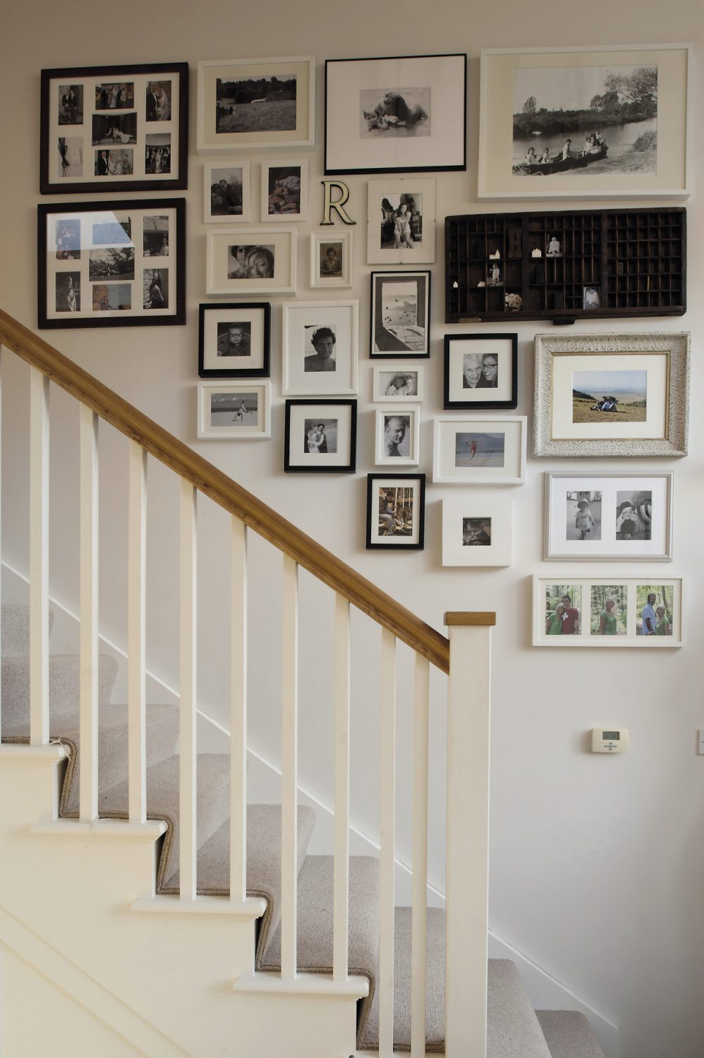 A wide array of family photographs line the ascent up the staircase