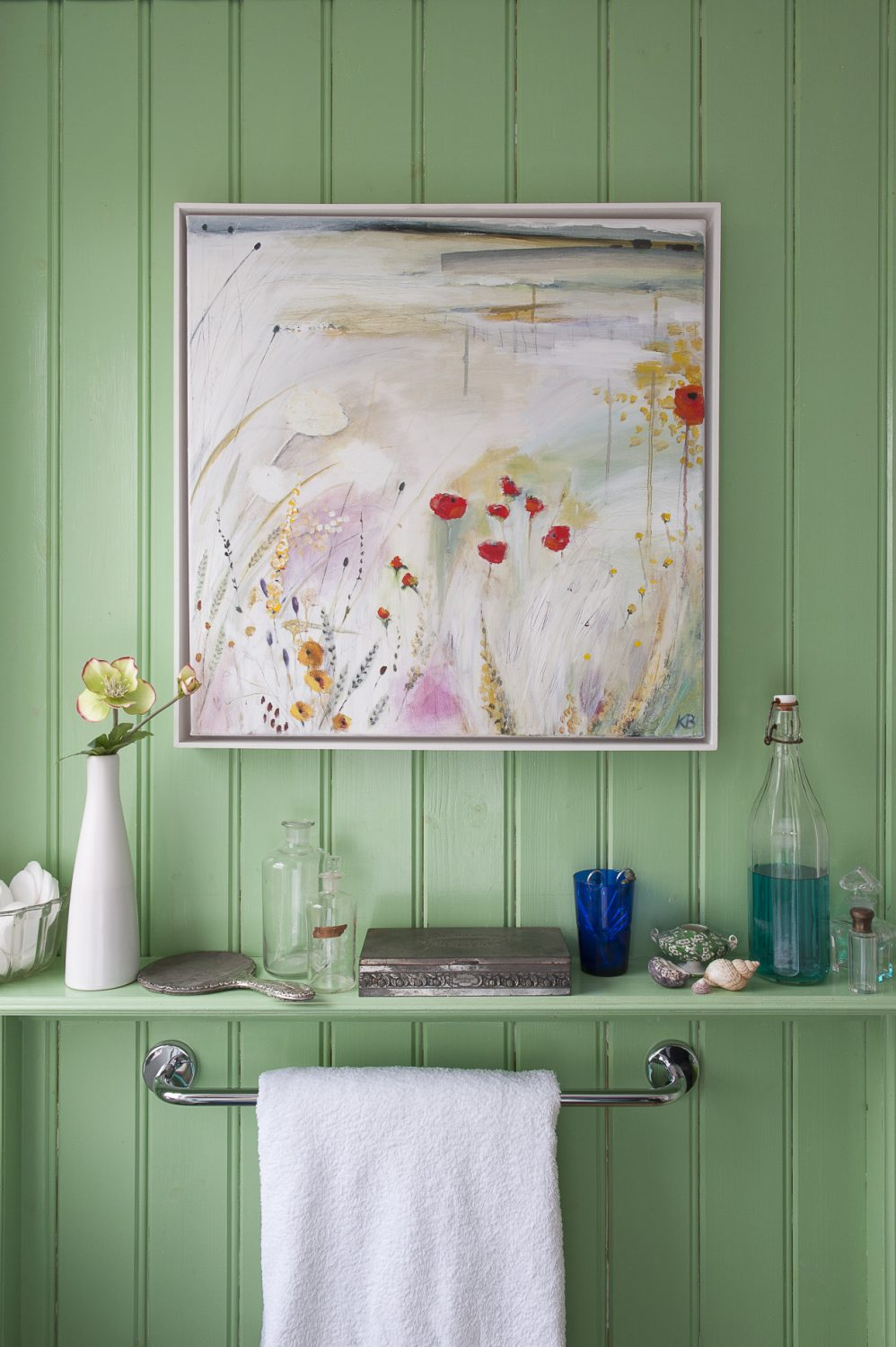 The full-height tongue and groove panelled walls of the family bathroom are painted a fresh apple green. Shelves around the room are lined with groups of apothecary bottles, found objects and shells