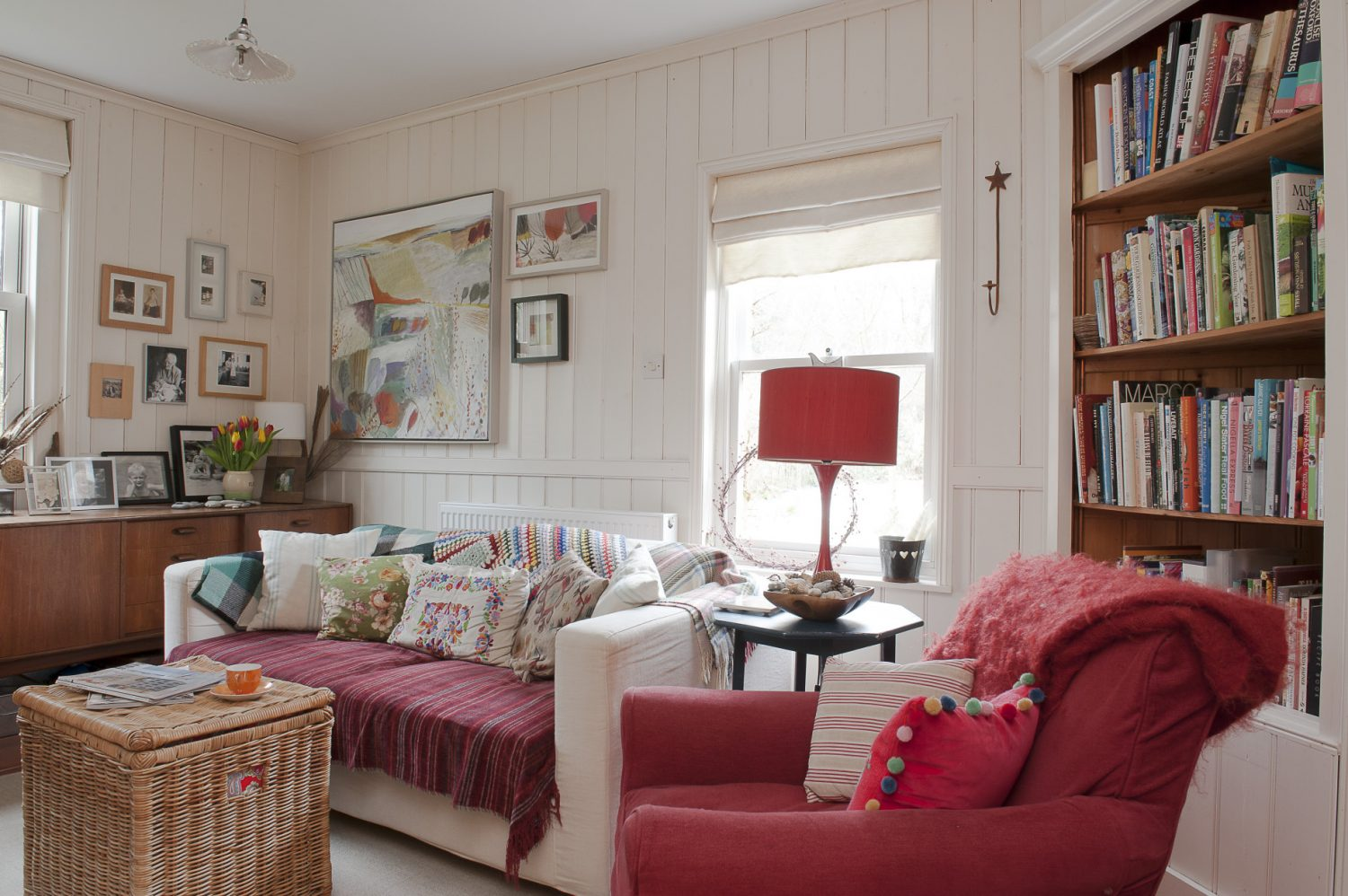 Next door to the drawing room is a wood-panelled snug that was once the kitchen. Dressed with colourful plump cushions and strong red accents, it makes an enticingly cosy retreat