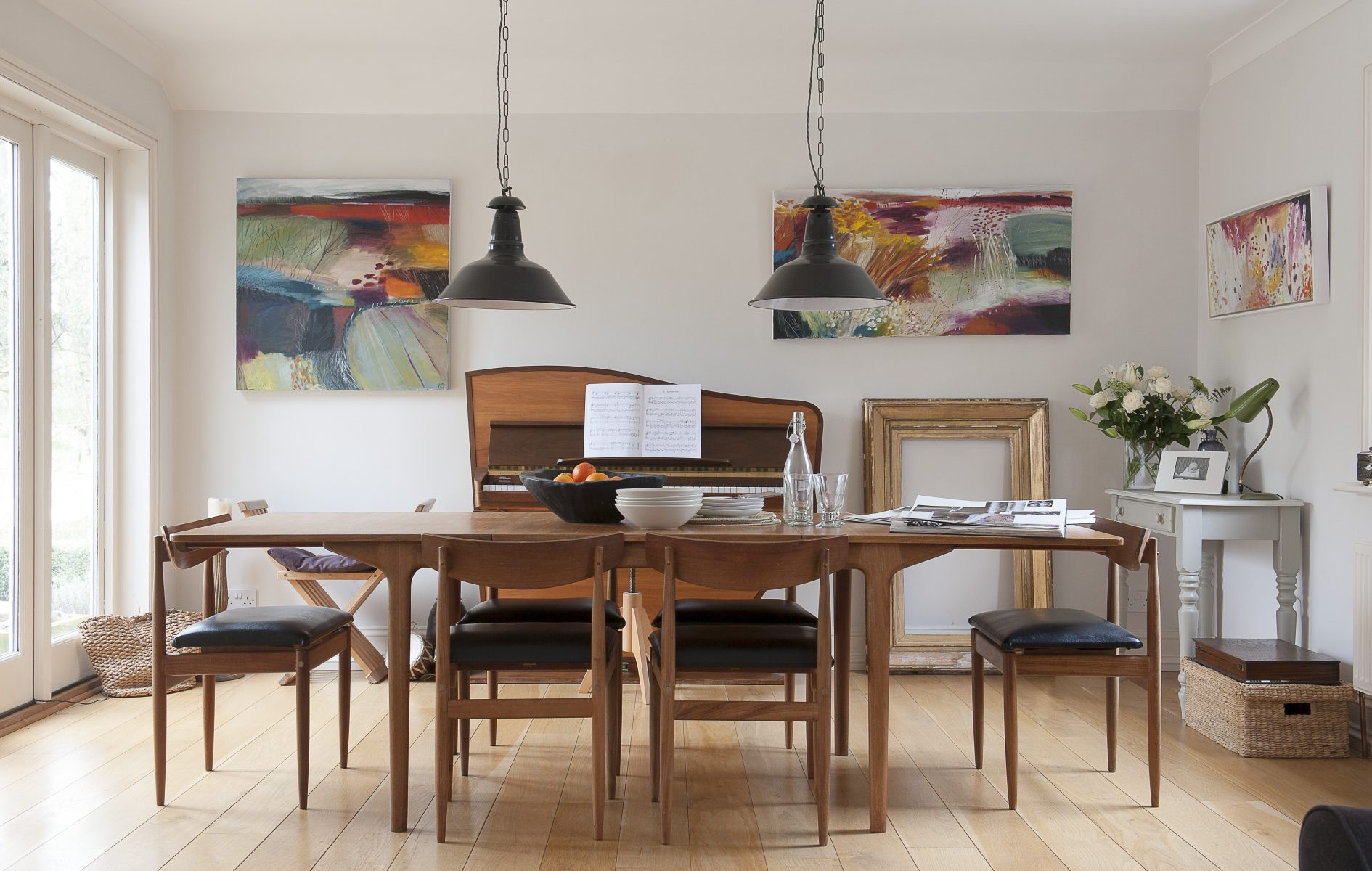 In the dining room, pride of place goes to the 1960s in the shape of a slim and elegant dining table over which hang a pair of old industrial lights from an antique shop in Hastings. Behind it is a wonderful '60s Dutch Rippen upright piano