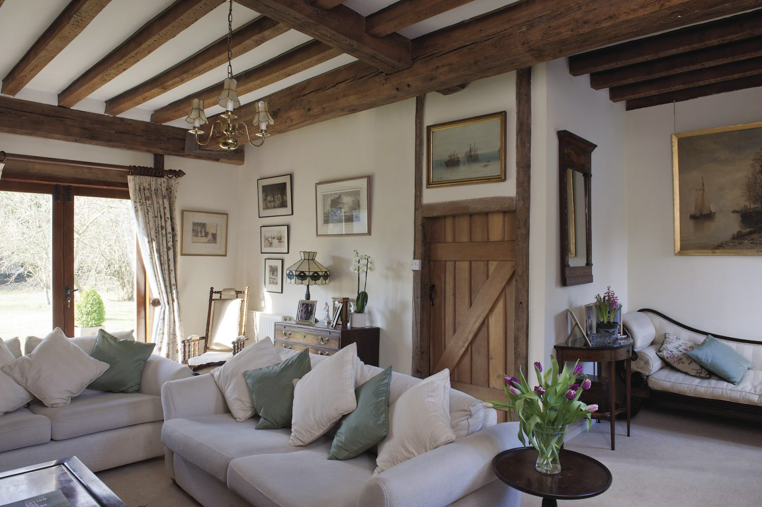 Two cream coloured sofas and a dainty armchair are set in front of the fire and scattered with sea green and ivory silk cushions