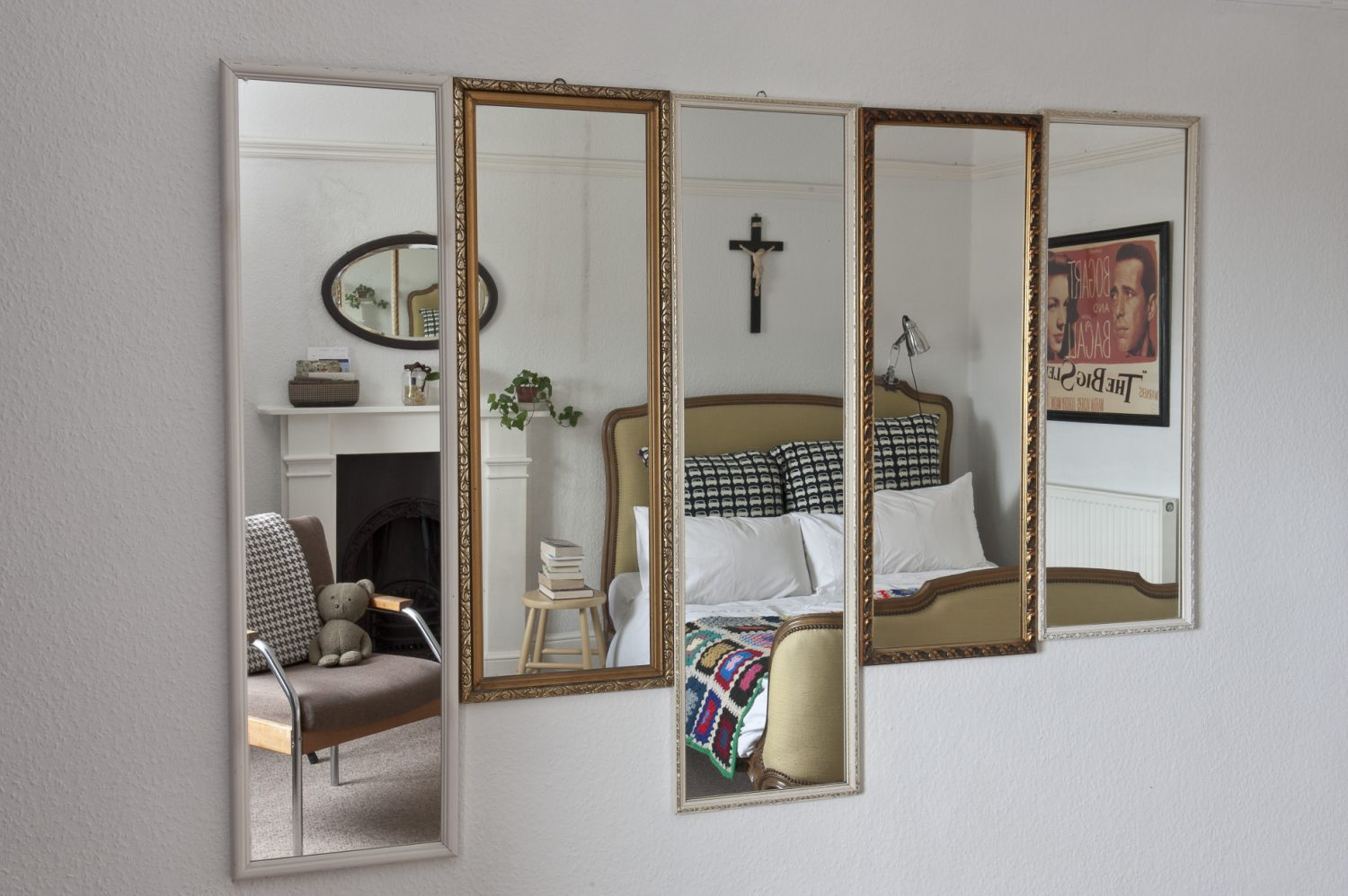 On the wall opposite there is a collection of five framed mirrors, all hung closely together so that they form a kind of panel