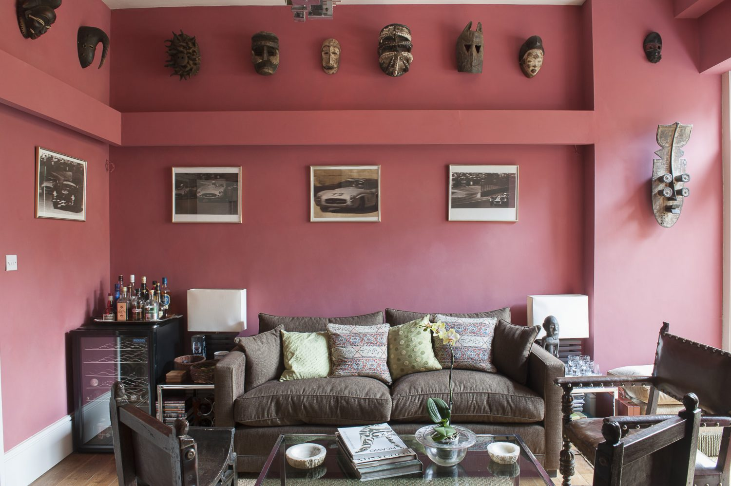 The rear reception room has been painted a deep, warm red, and is lit by a wonderful Italian chandelier. Wall lighting subtly illuminates the amazing tribal masks around the room that stare down from on high