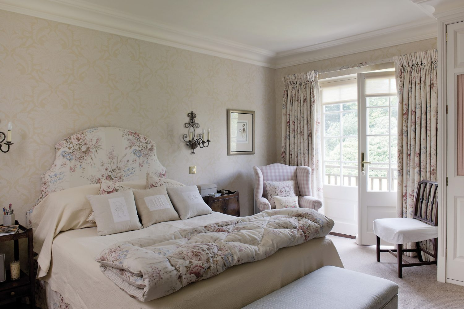 Ro's bedroom overlooks the garden and has French windows onto a small wooden balcony. The room is light and serene, with a pale wallpaper and a bedhead and curtains made of the same softly coloured chintz