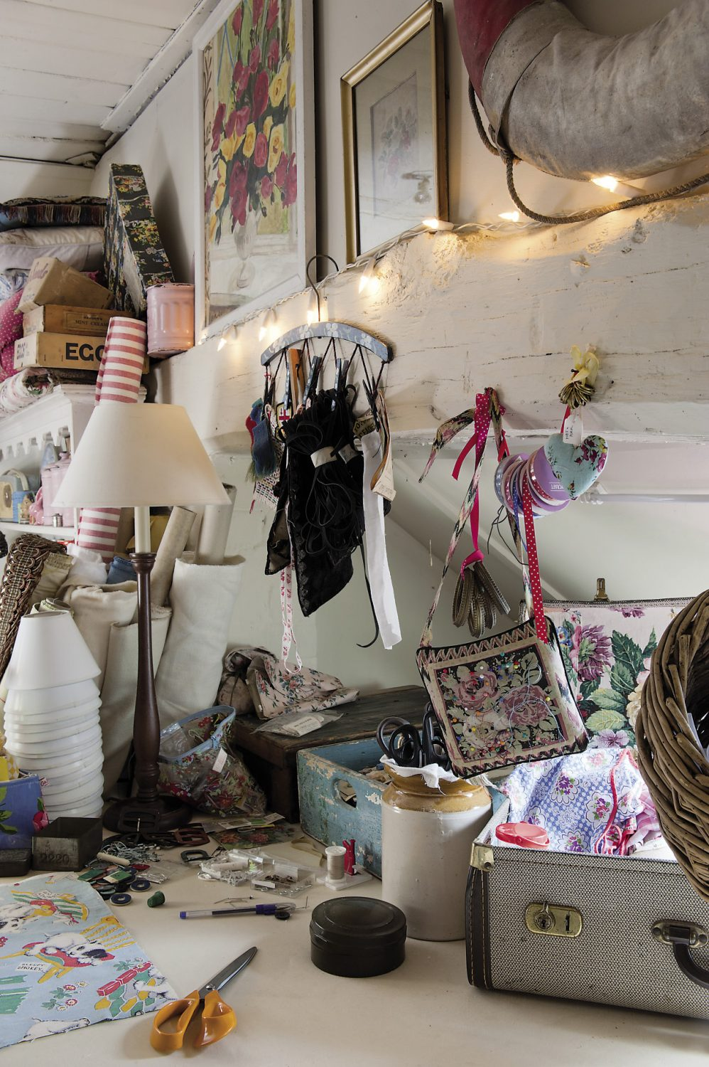 Madeline's workroom is artfully packed with cushions and fabrics, ribbons and buttons, irons and ironing boards