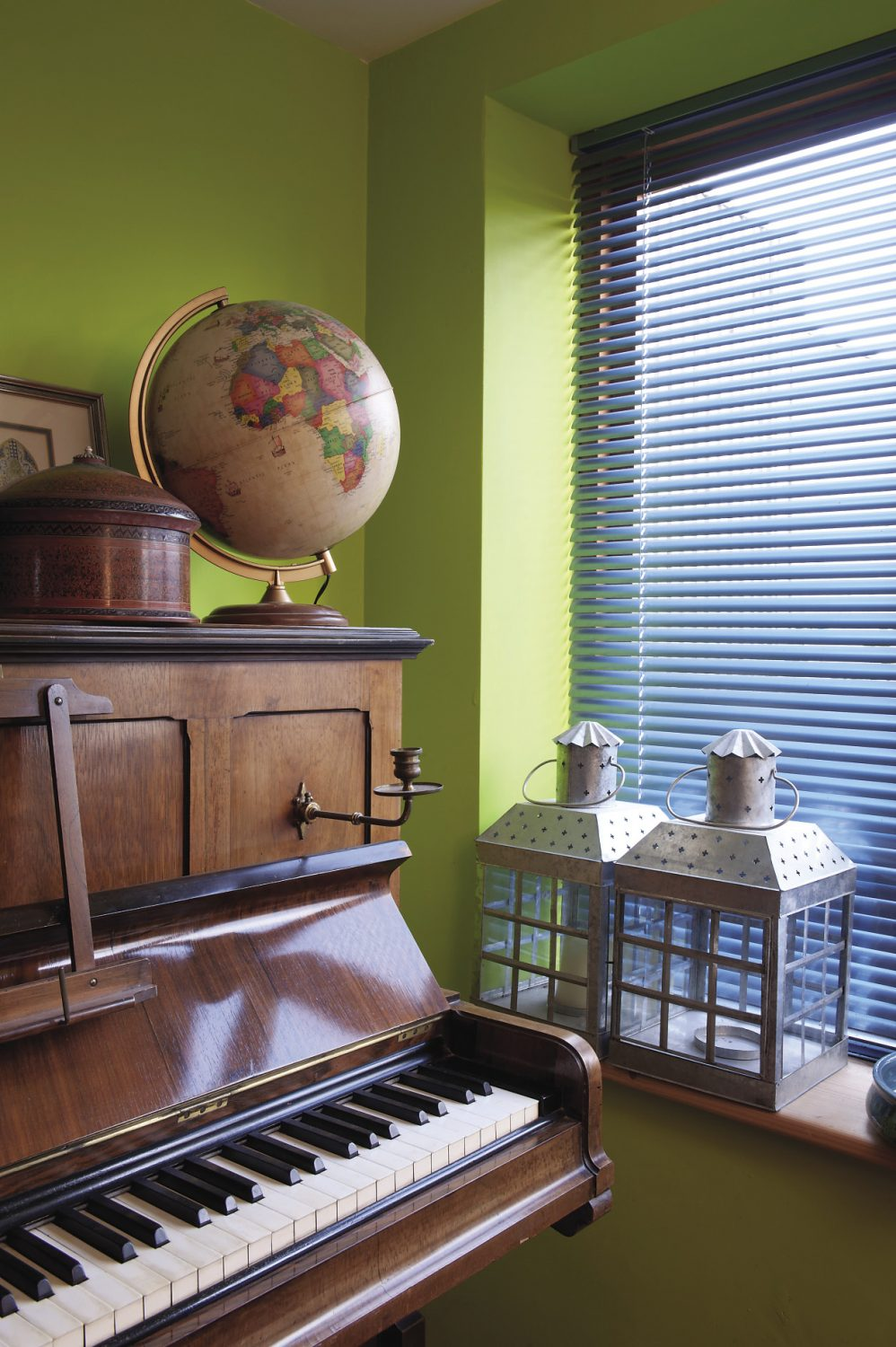The study, home to Oliver's floor-to-ceiling CD shelves, is painted a zingy lime green