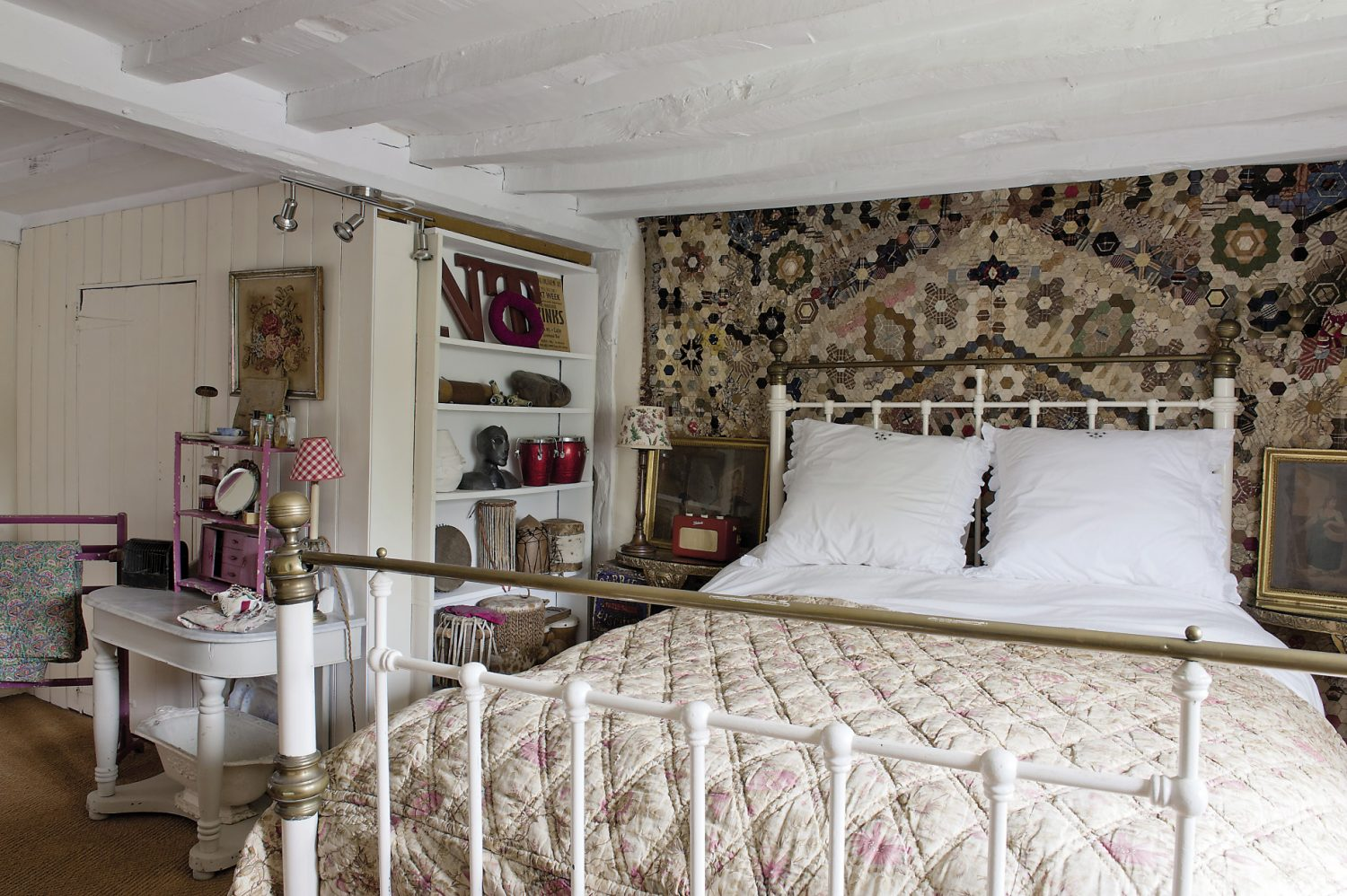 In the spare room, an intricate quilt has been used to create a wonderful wall hanging behind the head of the bed. Collections of neatly arranged objects line the shelves and the pale beams give the optical illusion of raising the ceiling height