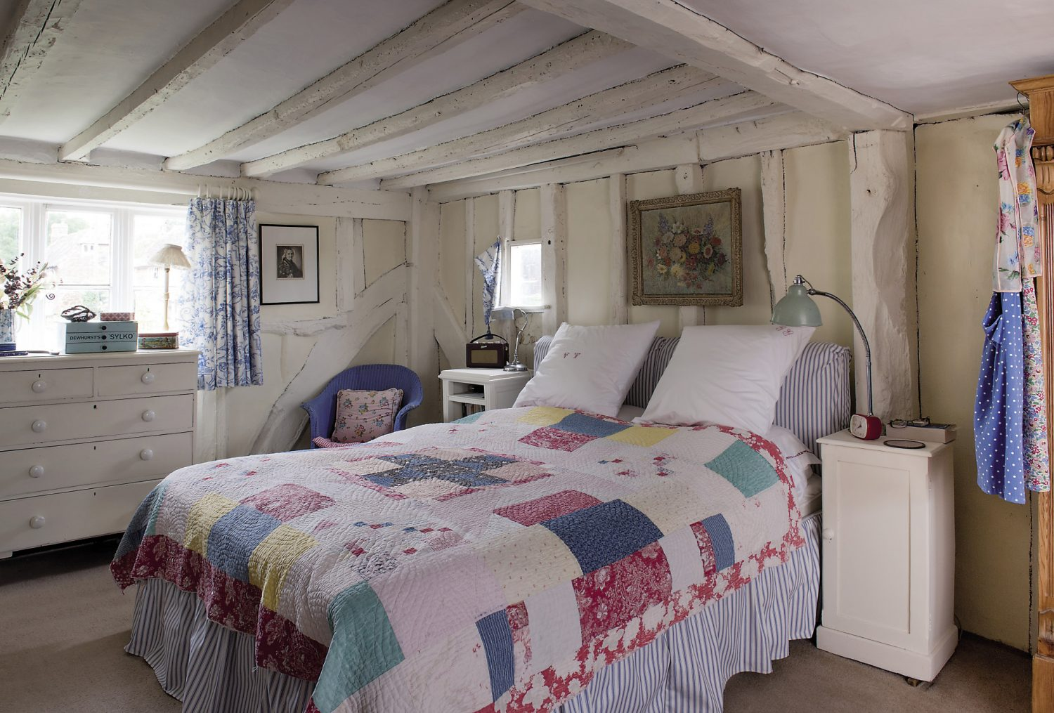 The bedrooms are full of vintage charm, with wonderful old patchwork quilts being used as wall hangings. On the beds are glorious quilts and, dotted among hats, scarves and bedroom bits and bobs are yet more neat piles of quaint old fabrics