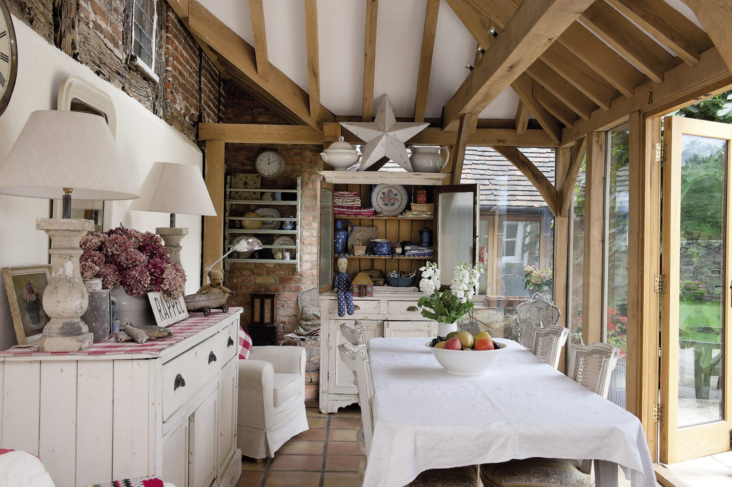 The oak-framed garden room extension at the back of the house brings a wonderful feeling of light and height to the ground floor. The weatherboarding has been removed from what would have been the outside wall, exposing original timber frame and the old bricks, which makes them into a charming feature of the room