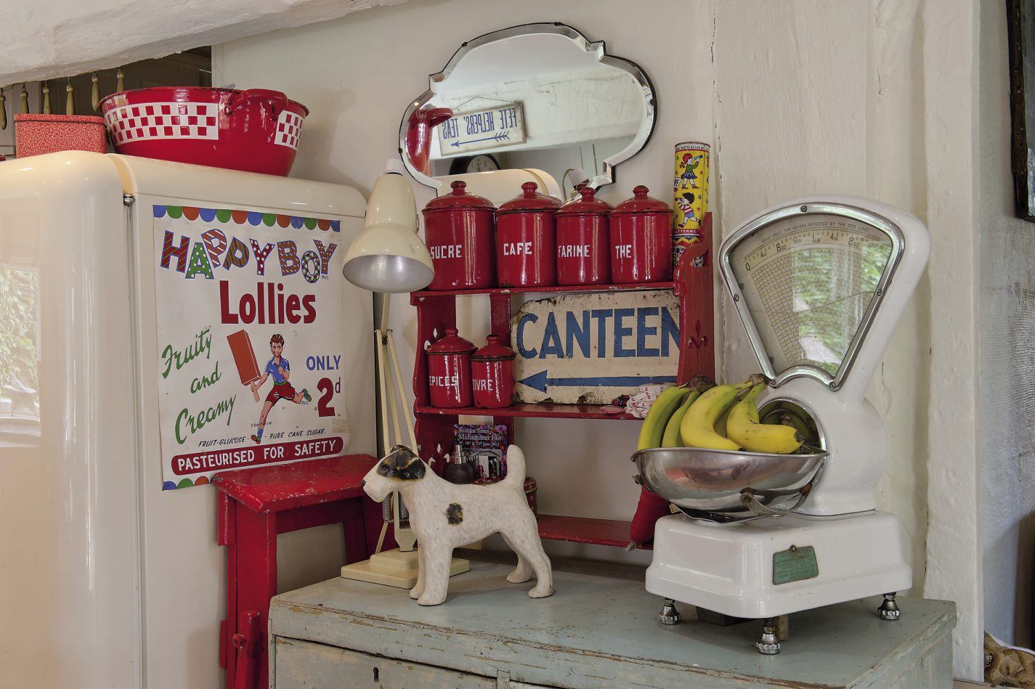 "Warm and friendly red is the accent colour in the kitchen in the form of vintage kitchen chairs and the quirky bits and bobs that Madeline has found at collector's fairs and boot sales. ""Old and original are the best. I love old fabrics and I'm really guided by colour. Red is my favourite,"" she says."