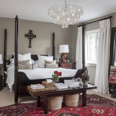 The simple, calm tones of Farrow & Ball Light Grey complement the Shiraz rug and four poster in the master bedroom