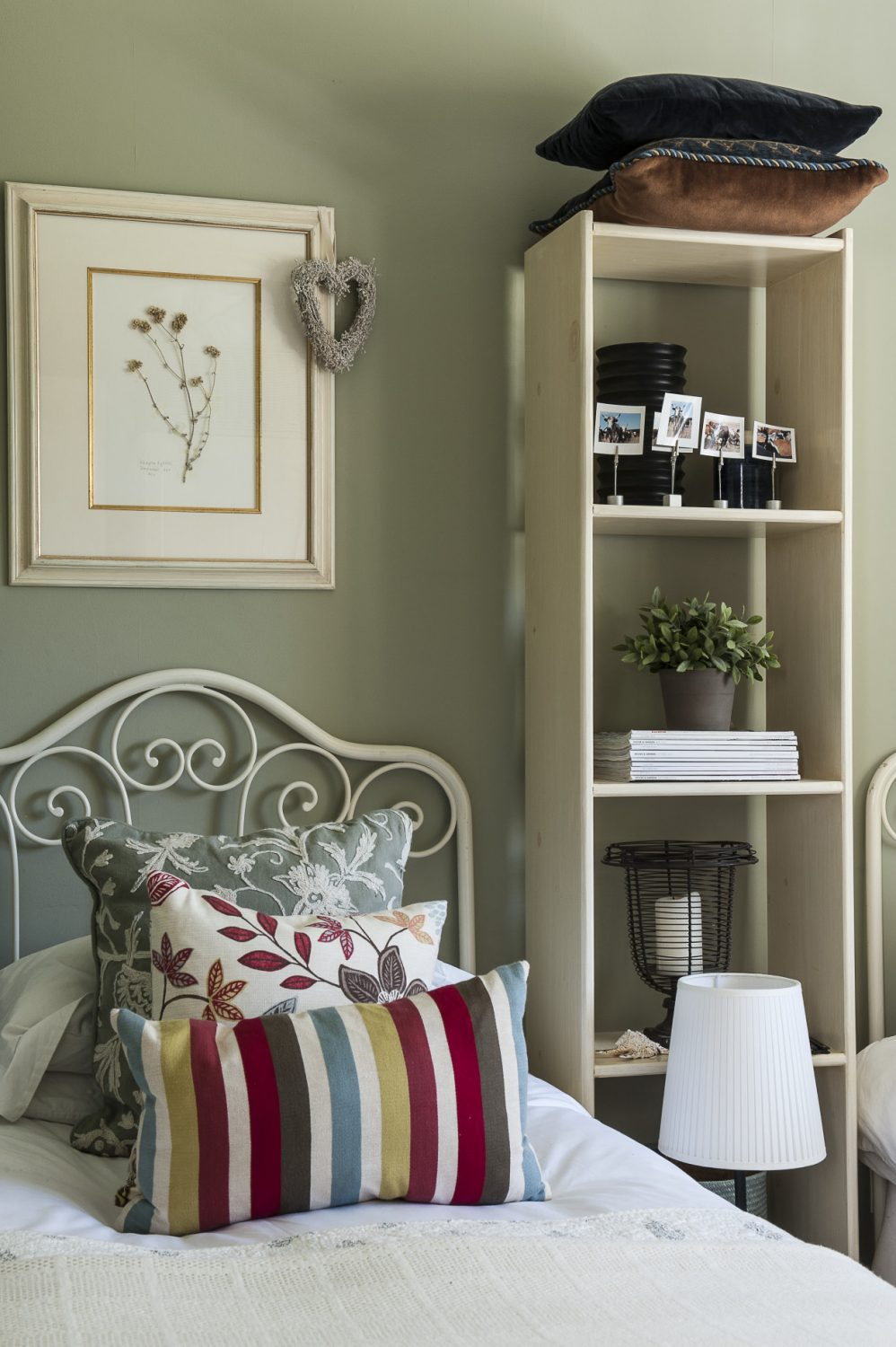 The bright second guest bedroom features delicate wrought-iron headpieces which are actually the matching head and foot of a single bed found in a Tunbridge Wells antique shop