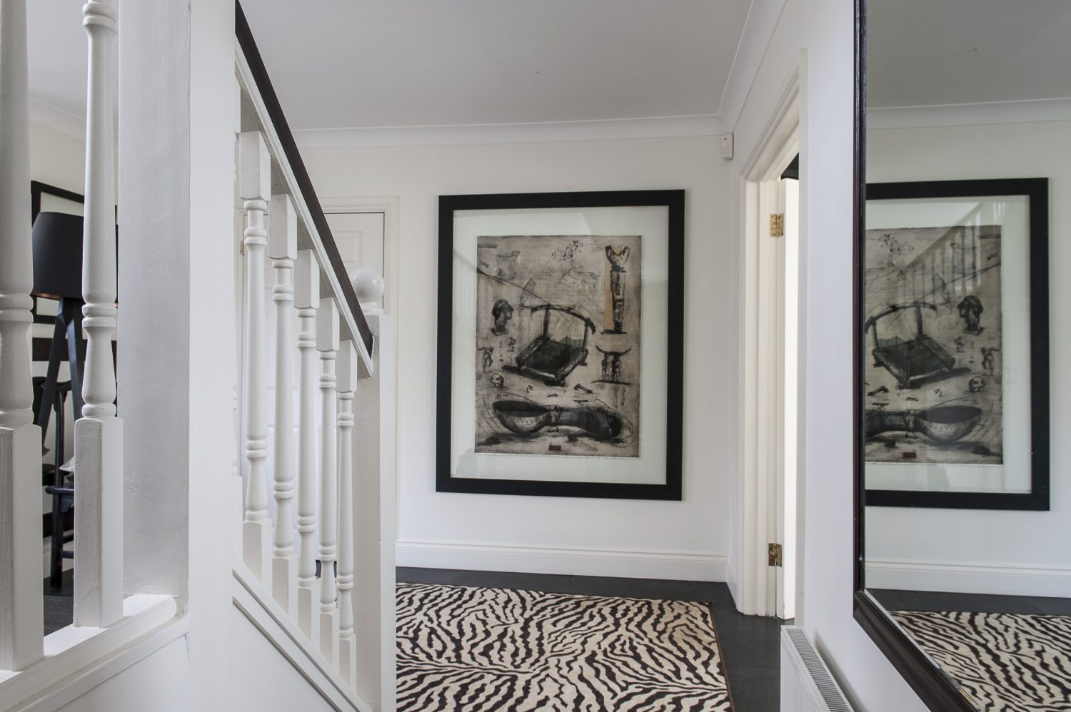 In the hallway sprawls a zebra print rug and on the wall a mixed media work by another RSA artist Debra Bell. In the children's room sofas – one stone, the other black – lounge around a huge TV. On the wall opposite is a pair of antlers and a great wildlife print by one of the couple's favourite artists, South African John Moore...