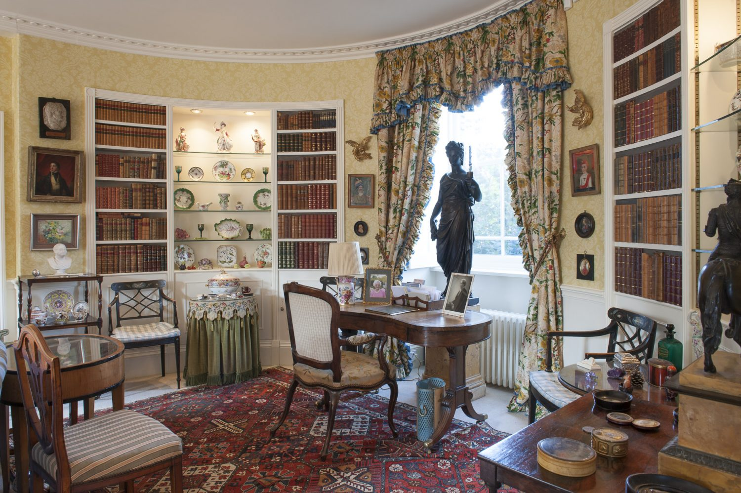 Today, the curved walls of the drawing room, created by a vicar in the nineteenth century, have bookshelves with hidden doors that silently open when pressed in the right spot