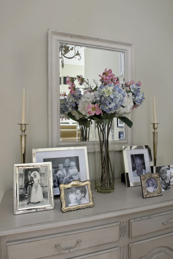 A handsome painted sideboard on the landing is covered with more silver-framed family photographs many of which feature Lucinda's parents