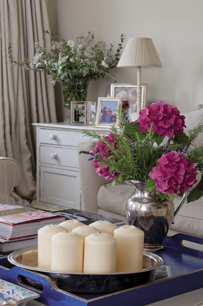 In the drawing room a large square coffee table from Woodcocks in Tenterden shows off neatly arranged piles of art books along with a silver vase filled with hydrangeas and branches of aromatic rosemary