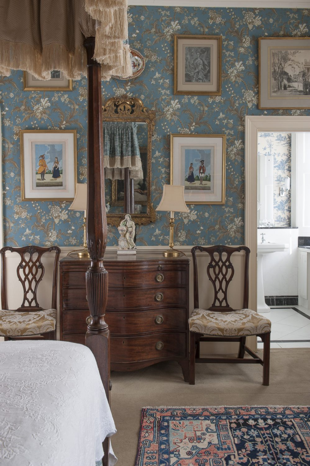 There are well-chosen pieces of walnut and mahogany furniture and a number of gilt mirrors and pictures including a modern oil