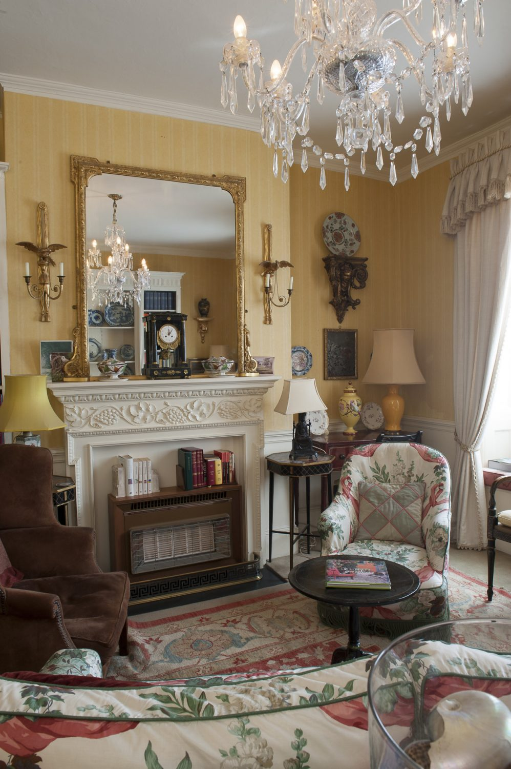 The walls have been covered in a warm yellow Colefax & Fowler stripe and the heavy herringbone patterned linen curtains reinforce the sense of discreet luxury