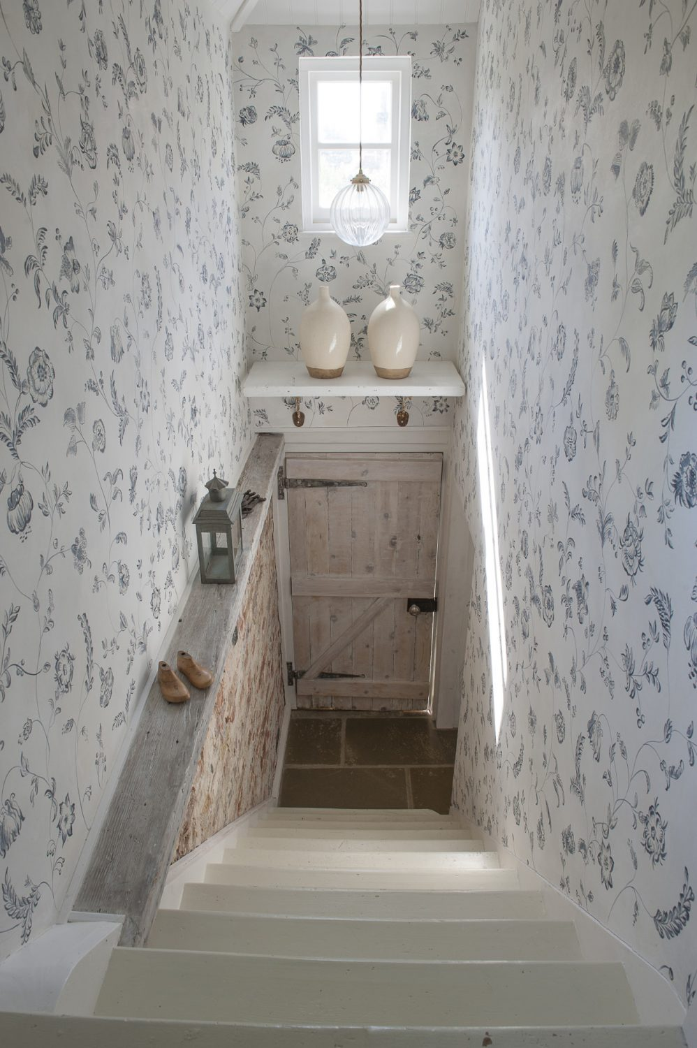 Original brickwork has been exposed below the painted walls on the ascent up the staircase