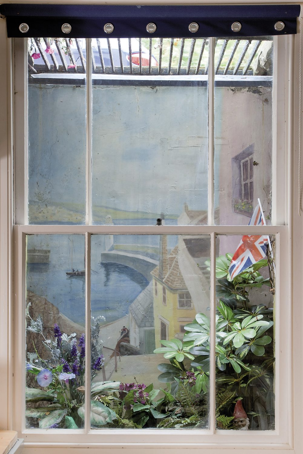 The kitchen, being at the front of the house is situated below ground with a lightwell rather than a view. To compensate for this, Alastair planted ferns in the base and his friend Linda King painted a mural on the wall behind
