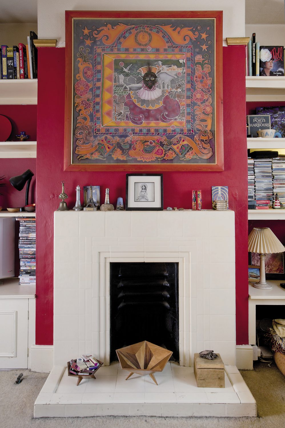 The sitting room is painted a rich, British red with a gold picture rail. Alastair's love of travel is evident throughout the room, from the oriental rug on the floor to the kilim-style printed fabric that covers the armchair