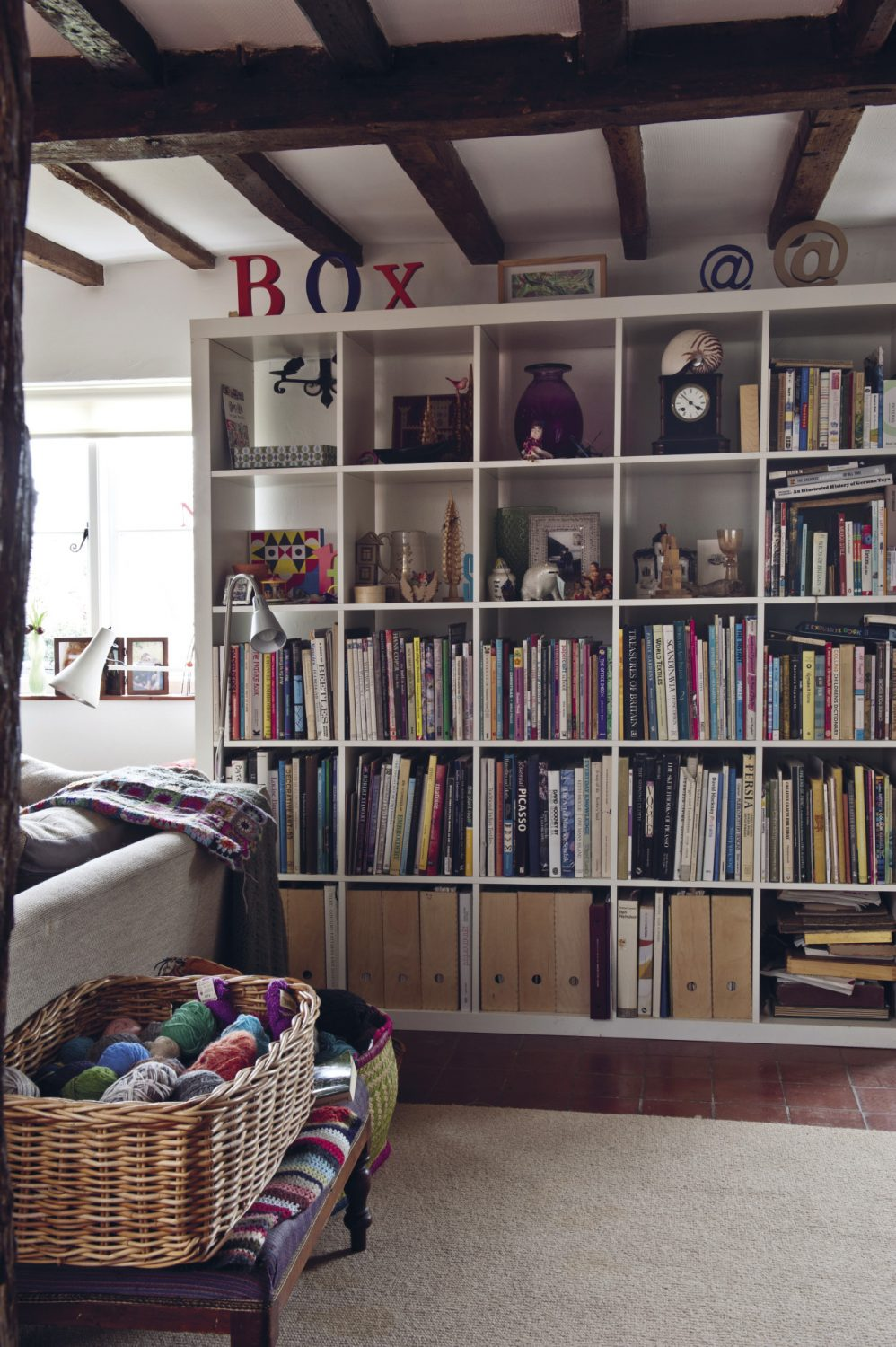 Two sides of the room are covered with shelves with books, files and vintage wooden toys