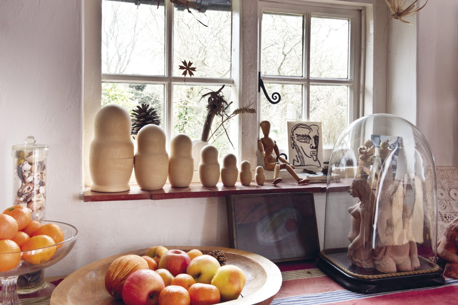 A wooden artist's dummy sits among the other interesting pieces on a windowsill