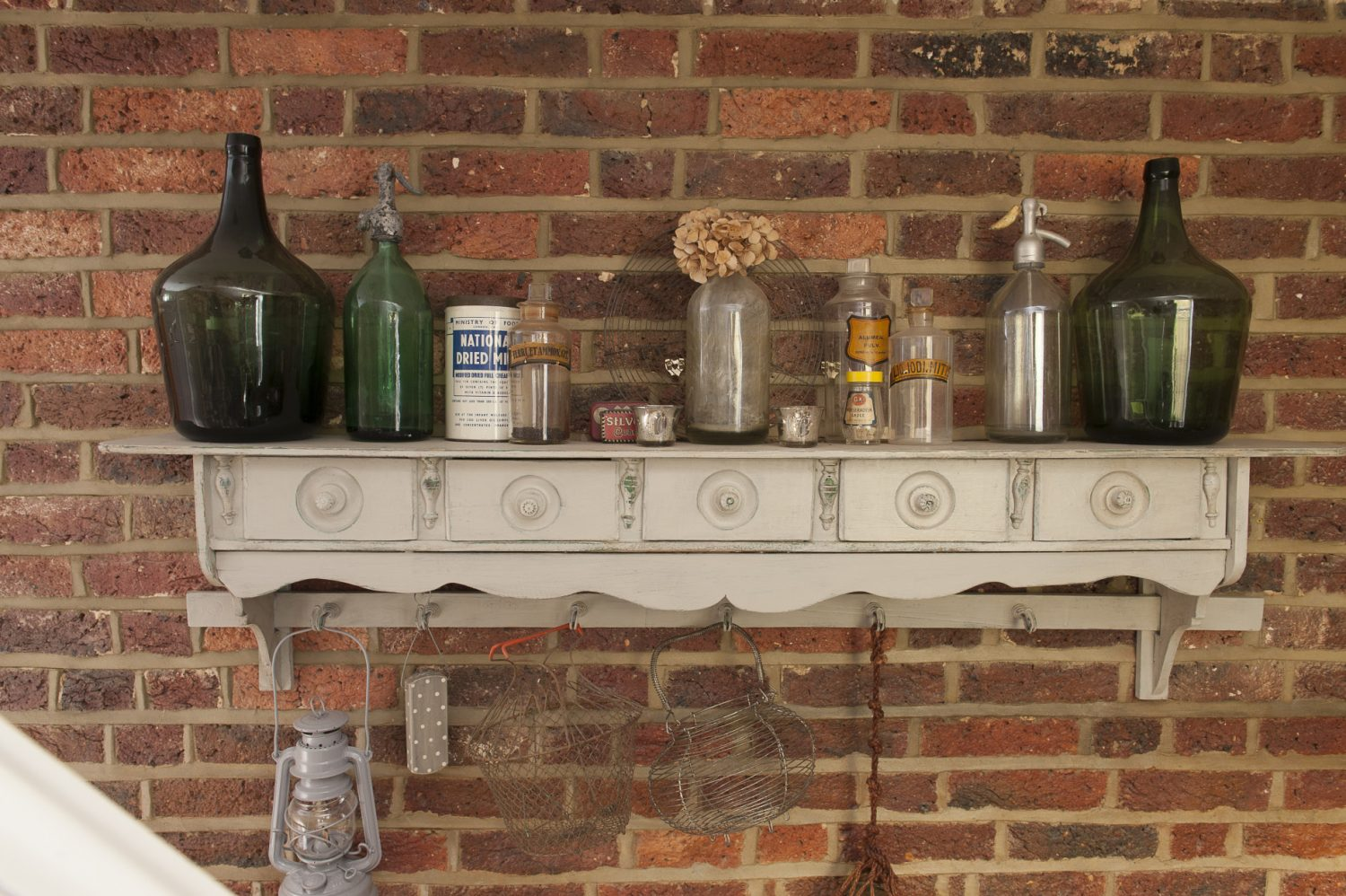 On the way up to the ground floor visitors pass a wooden case of old soda siphon bottles and a pretty drawered shelf on which stands a collection of soda siphons and some fat green bottles