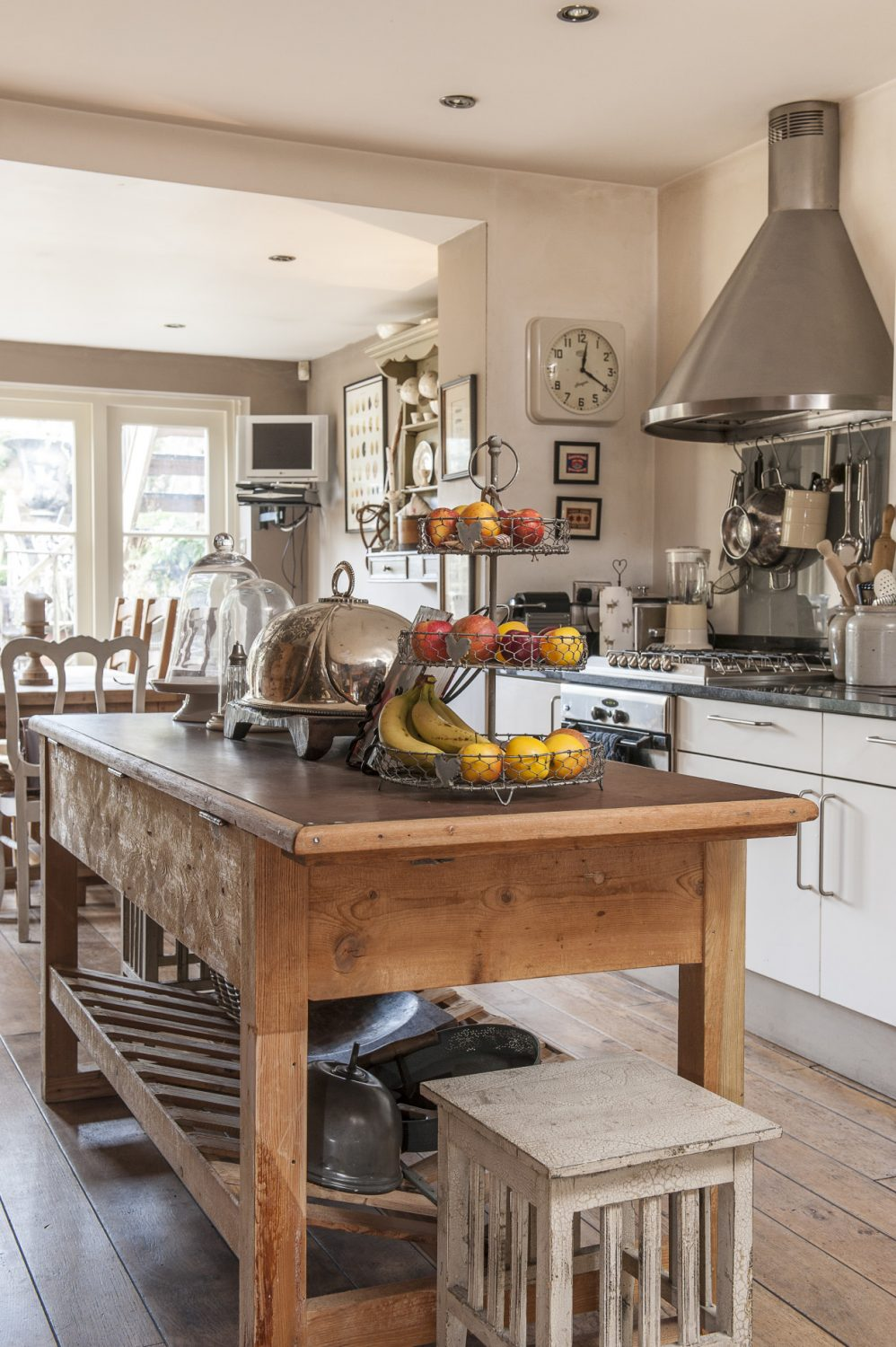 The kitchen section is divided invisibly down the middle – the business side all black granite and steel and the other a far warmer world of soft shades, shadows and antique wood