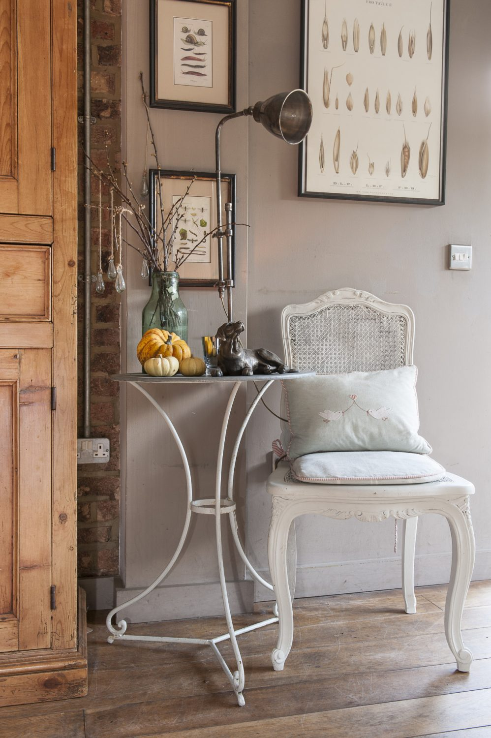 The dining room gathers round a bespoke bleached oak table and an eclectic collection of white-painted and old bare wood chairs