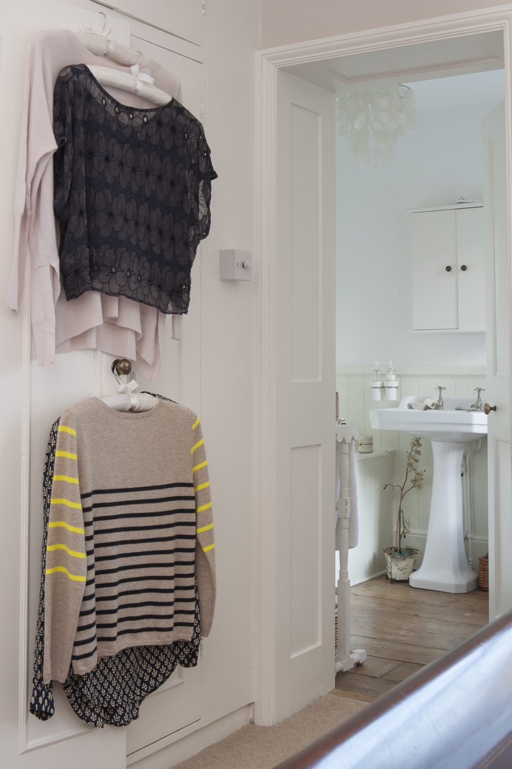 The master bedroom en suite. On a cupboard door hang examples of the clothing offered by Hall & Co in Otford