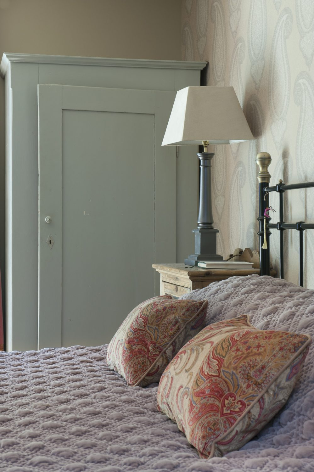 The basement guestroom features a Victorian style brass bedstead and distressed bedside units from Foxhole Antiques