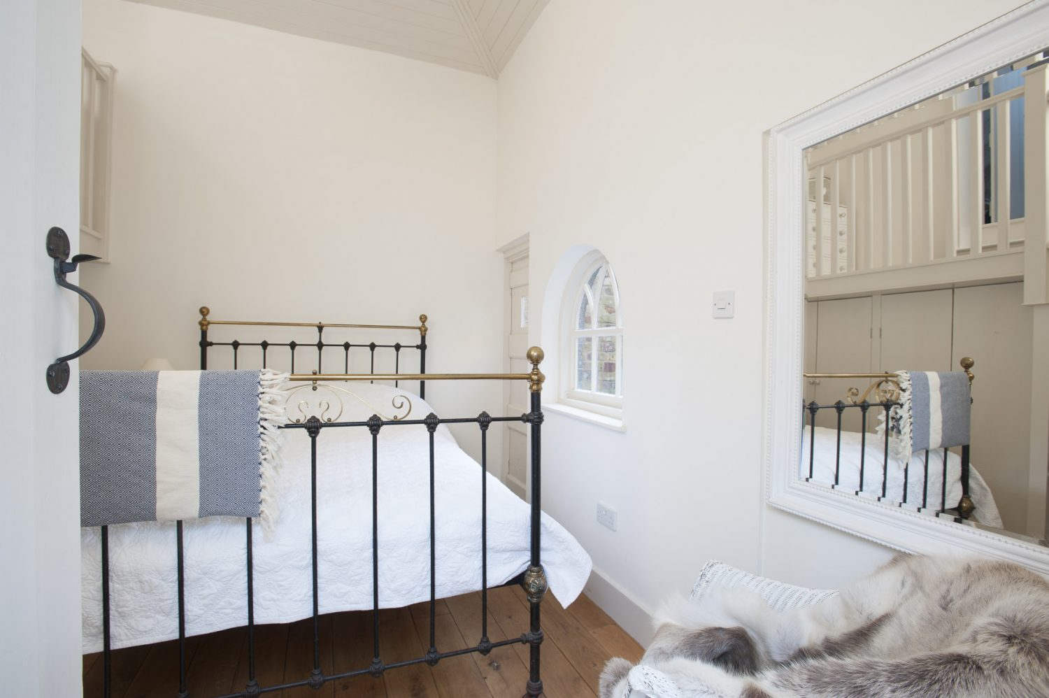 The original shed has been converted into a cosy white-on-white guest bedroom with a brass and iron bedstead