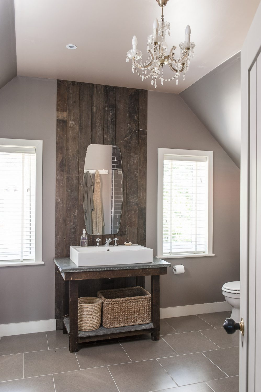 The bathroom is a gentle mushroom with cool white woodwork. The basin sits on an antique lead-topped table backed by a ceiling height panel made from reclaimed floorboards