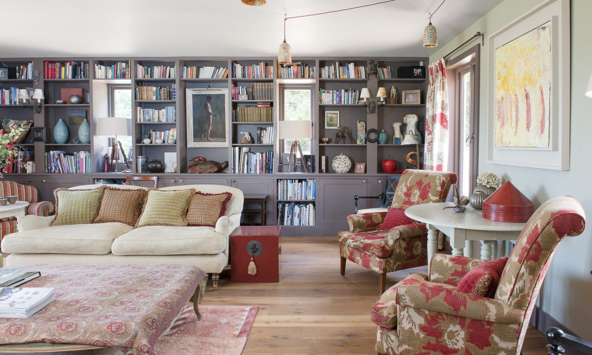 The double aspect drawing room runs the depth of the house and features bookshelves that span the length of one wall