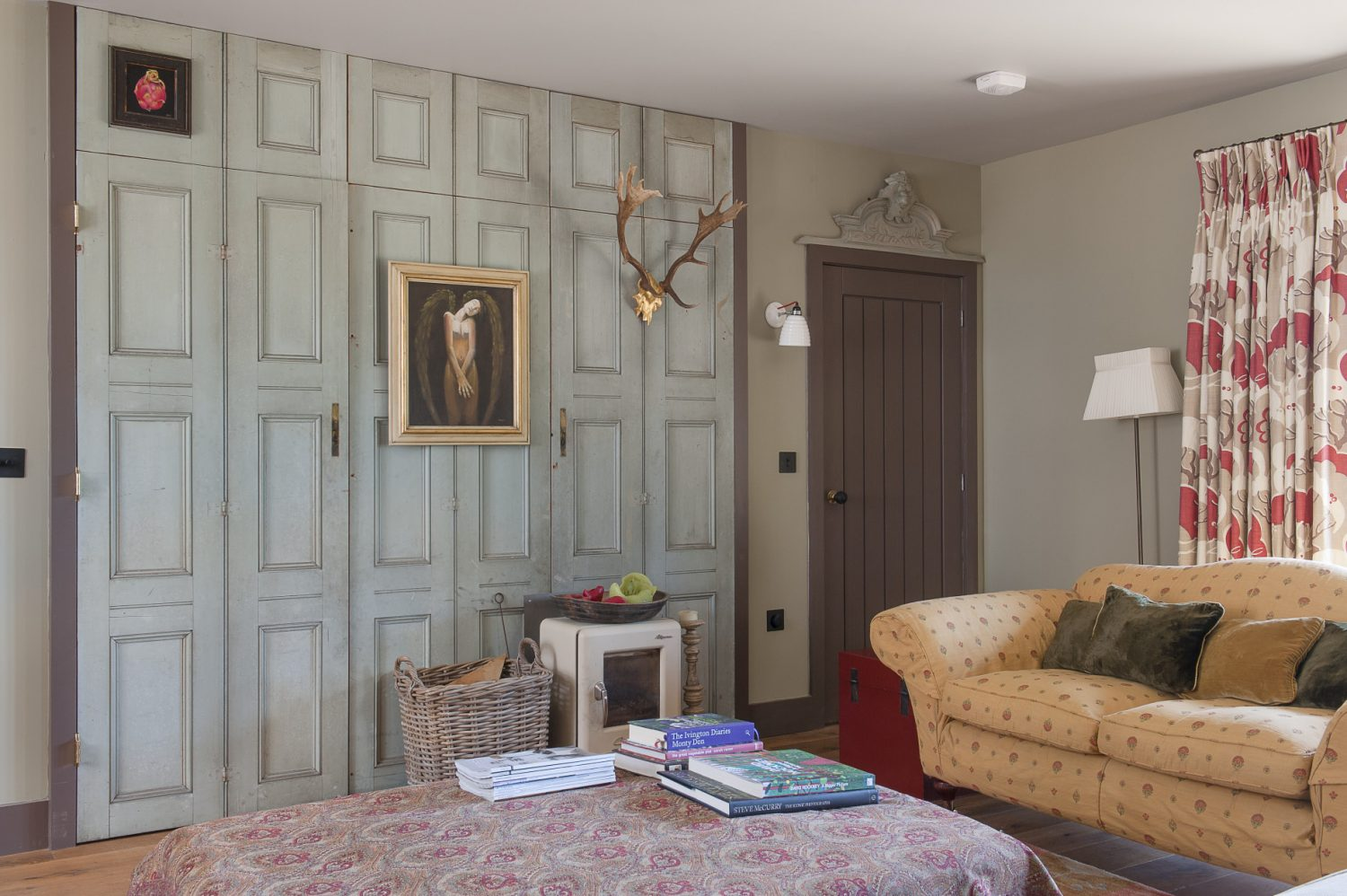 In the drawing room a set of former French room dividers, that cleverly conceal the television, sport a fetching pair of golden antlers