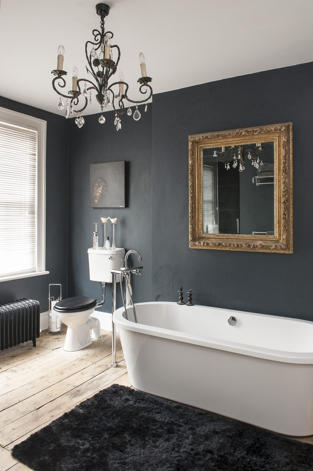 The juxtaposition of light and dark in this house is emphasised in the bathrooms. There are two good-sized rooms – one white and one black – both have a striking painting in a similar position; in the white bathroom there's a picture of a skull by Ben Eine and in the black, a raw and intense painting by Alice Maylam titled 'Out of the Dark' which features a face protruding into the light and provided the inspiration for Rob's bold colour choice...
