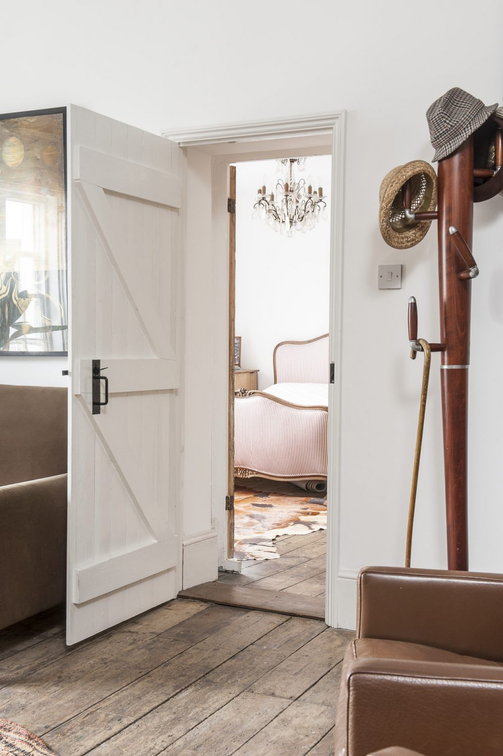 A door from the living room leads into the master bedroom. Rob has seamlessly combined an eclectic mix of contemporary and antique in each room